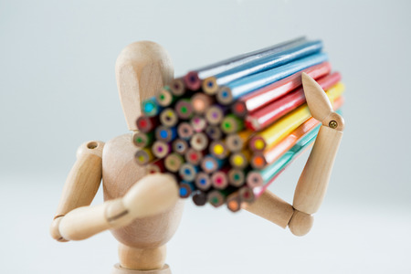 artists dummies: Wooden figurine carrying bunch of pencils against white background