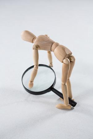 arte optico: figurilla de madera recogiendo de una lupa sobre fondo blanco