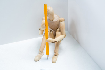 Tensed wooden figurine with a pencil sitting against wall