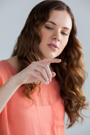 invisible: Woman pretending to touch an invisible screen against grey background