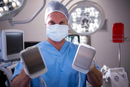 resuscitate: Portrait of male surgeon holding defibrillator at the hospital