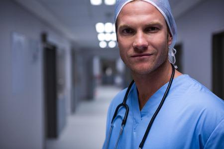 Portrait of surgeon standing in corridor at hospital