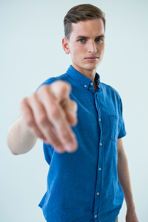 invisible: Portrait of man touching an invisible screen against white background