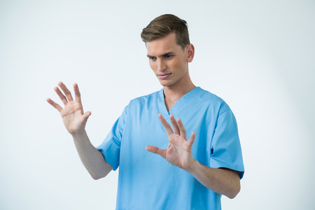invisible: Male nurse touching an invisible screen against white background Stock Photo