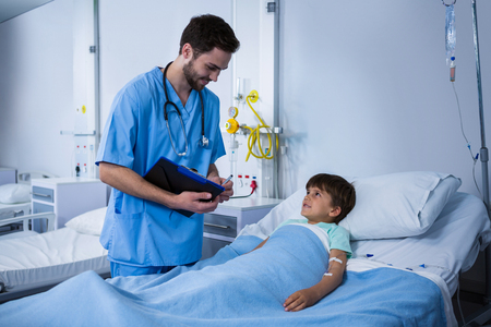 Male nurse interacting with patient during visit in ward at hospital