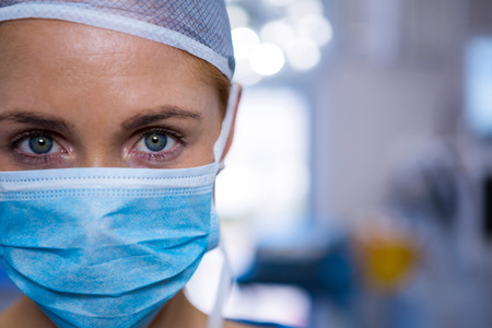 surgical mask woman: Portrait of female surgeon wearing surgical mask in operation theater at hospital