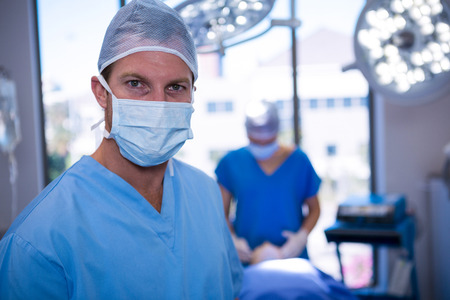surgical mask: Portrait of male nurse wearing surgical mask in operation theater at hospital