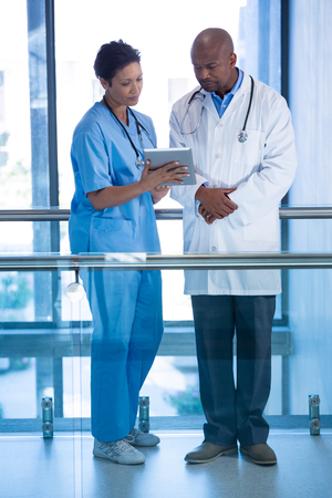 Male doctor and nurse using digital tablet in corridor at hospital Stock Photo