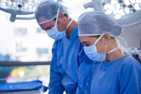 surgical mask woman: Female and male surgeon wearing surgical mask in operation theater at hospital