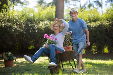 Senior paar spelen met een kruiwagen in de tuin op een zonnige dag