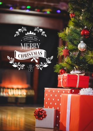Digitally composite image of merry christmas sign against christmas tree and gifts Stock Photo