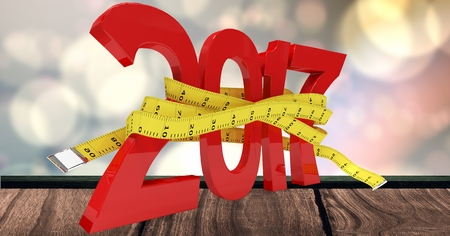 numeracy: 2017 wrapped with measure tape on wooden plank against a composite image 3D of bright bokeh lights Stock Photo