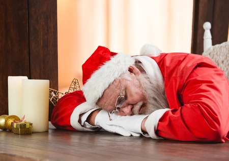 entertaiment: Santa claus sleeping on a wooden table at home