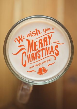 froth: Digitally composite christmas and new year wishes on coffee froth on wooden table Stock Photo