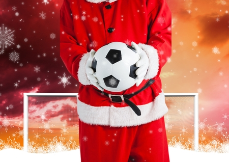 Mid section of santa claus holding a soccer ball against goal post