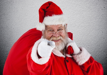 entertaiment: Santa claus with gift sack pointing towards camera aganist grey background