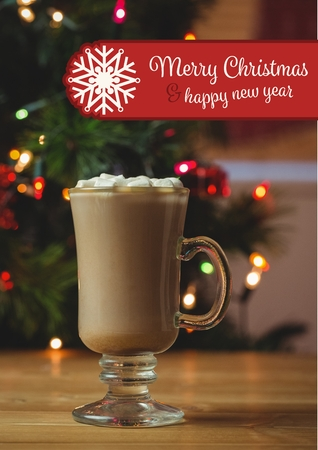 Composite image of merry christmas and happy new year wishes with cup of hot chocolate on wooden table
