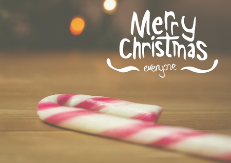 Digitally composite image of merry christmas with candy cane on wooden table
