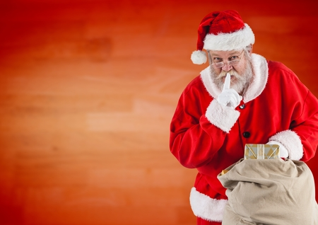 Santa claus holding gift sack with finger on lip against red background