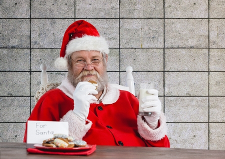 entertaiment: Portrait of santa claus having his meal against brick wall Stock Photo