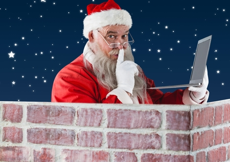 secrete: Portrait of santa with finger on lip using laptop against digitally generated night background Stock Photo