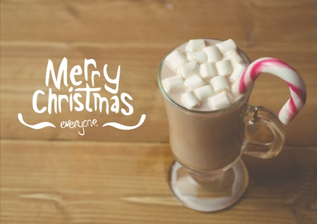 Digitally composite image of merry christmas against a cup of hot chocolate with marshmallows and candy cane