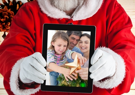 Santa claus holding a digital tablet with photo of christmas family against wooden background photo