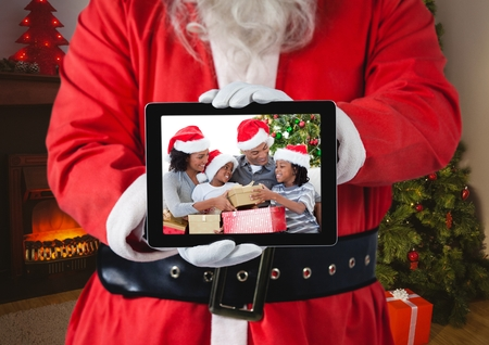 Santa claus holding a digital tablet with photo of christmas family at home photo