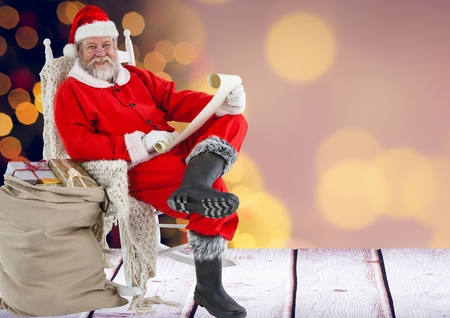 entertaiment: Portrait of santa claus holding wish list with sack of gifts against bokeh lights