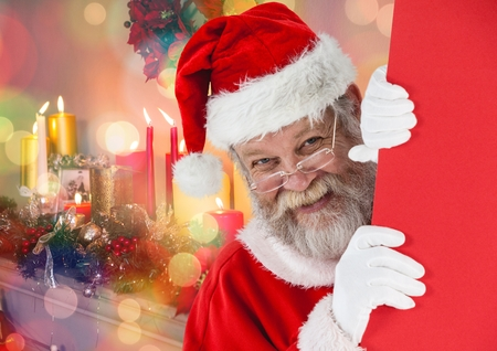 Santa peeking out from behind the wall against digitally generated christmas background Stock Photo