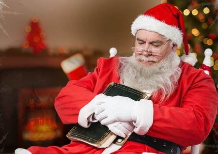 Santa claus with a diary sleeping on a chair at home