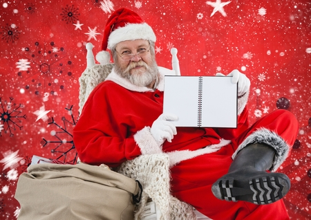 Santa sitting on chair and showing diary against digitally generated christmas background Stock Photo