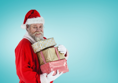Santa claus holding stack of christmas gifts against blue background Stock Photo