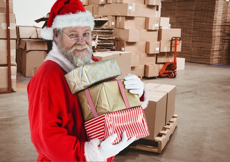 frohe: Santa claus holding stack of christmas gifts in warehouse full of boxes