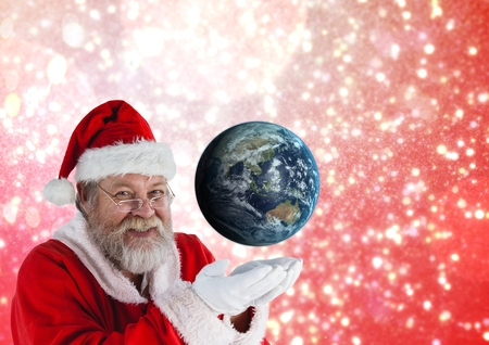 Smiling santa claus pretending to hold globe against illuminated background