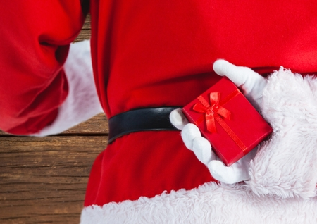 Mid section of santa claus holding a gift box