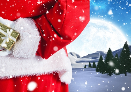 Santa hiding christmas gift behind his back against digitally generated snowy background Stock Photo