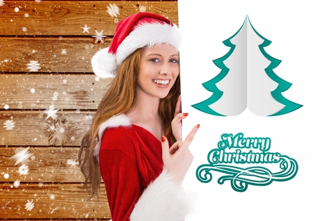 enjoyment: Smiling woman in santa costume pointing at placard wishing merry christmas