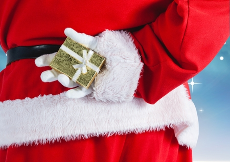 Mid-section of santa claus hiding gift behind his back Stock Photo