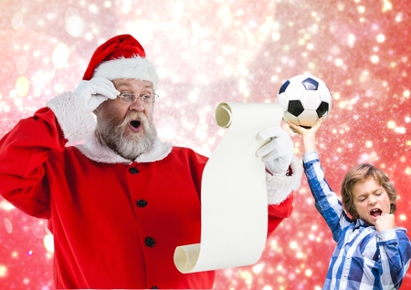 wish  list: Santa claus reading wish list and excited boy with football against digitally generated background