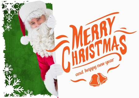 Santa clause peeking out from placard with christmas greetings Stock Photo