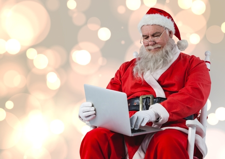 Santa sitting on chair and using laptop against bokeh lights background