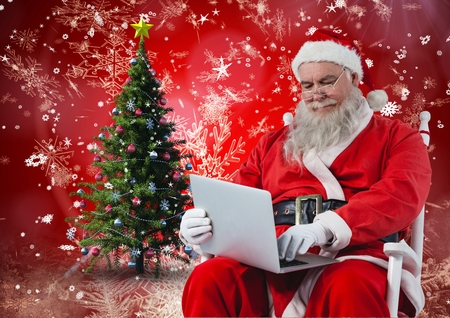 chrstmas: Santa sitting on chair and using laptop against digitally generated christmas background Stock Photo