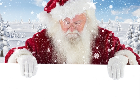 Santa claus looking down at white placard against digitally generated snowy background Stock Photo