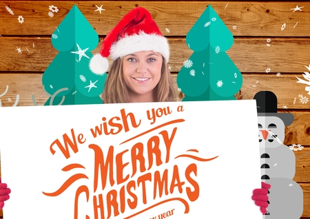 Beautiful woman in santa hat holding placard against digitally generated christmas background Stock Photo