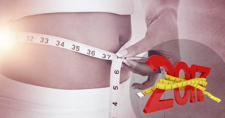 Mid section of woman measuring her waist against 2017 Stock Photo