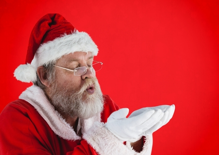 Santa claus pretending to blow imaginary snow against red background Stock Photo