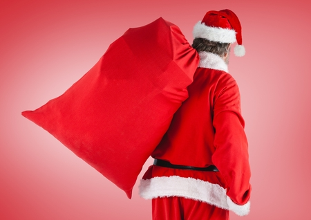 Rear view of santa claus holding gift bag standing against red background