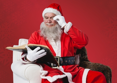 reading bible: Santa claus sitting on chair and reading bible Stock Photo