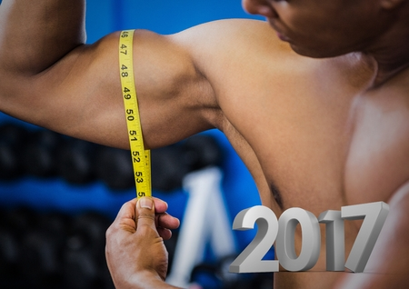 Close-up of man measuring his bicep against 2017 Stock Photo